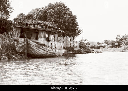 Black and white photo add texture vintage style of the old damaged wooden boat beached on the waterfront for background - Stock Image