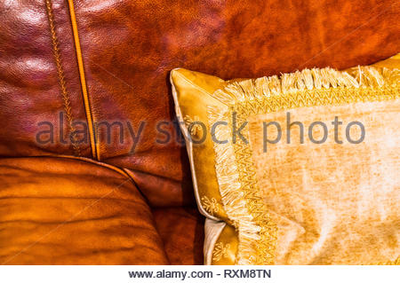Gold coloured pillow laying on a brown leather sofa. - Stock Image