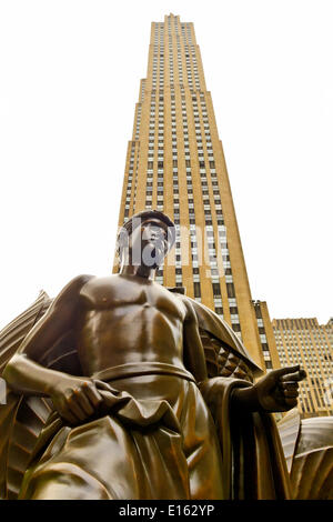 Manhattan, New York, U.S. - May 21, 2014 - At Rockefeller Plaza is bronze Mankind statue, Youth, by artist Paul Manship, with 30 Rockefeller Center looms behind, during a pleasant Spring Day, though skies are cloudy. - Stock Image