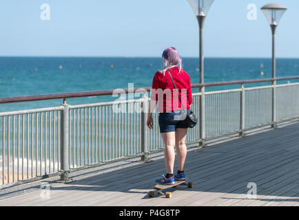 Bournemouth, UK. 22nd June 2018. UK sunny weather, a girl with pink hair skateboards down Boscombe pier in Bournemouth. Thomas Faull/Alamy Live News - Stock Image