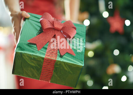 green Christmas present box in a hand of woman in red dress near Christmas tree - Stock Image