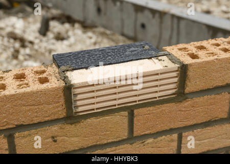 Plastic air brick vent in the partially built wall of a house - Stock Image