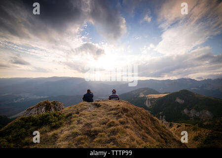 Rear view of men sitting on mountain against cloudy sky - Stock Image