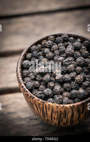organic kampot dried black pepper corns in traditional wood bowl in cambodia - Stock Image