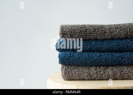 Stack of clean folded navy blue beige terry towels on wooden char gray wall background. Laundry spa wellness cleanliness concept. Scandinavian style.  - Stock Image
