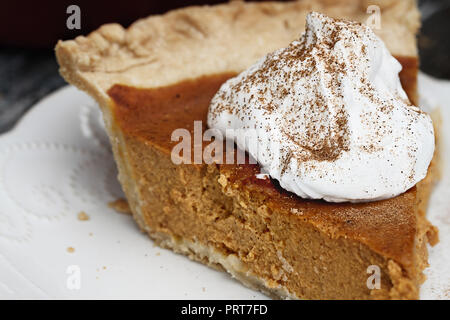 Slice of homemade pumpkin pie with topping and sprinkled with pumpkin pie spice. Extreme shallow depth of field with selective focus on whipped cream. - Stock Image