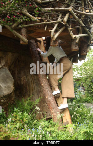 The Duchess of Cambridge climbs the ladder into the treehouse during a visit to her garden at the RHS Chelsea Flower Show at the Royal Hospital Chelsea, London. - Stock Image