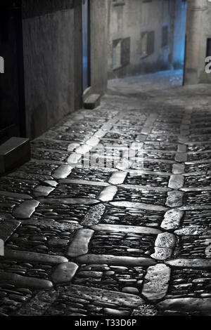 Lamps and stone cobbles at night in cobbled street alleyway in Erice, Sicily, Italy - Stock Image