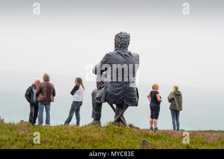 Hikers chatting by the Seated Man Sculpture by artist Sean Henry on Castleton in the North Yorkshire Moors National Park overlooking Westerdale - Stock Image