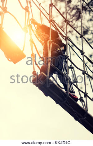 boy walking along rope bridge - Stock Image