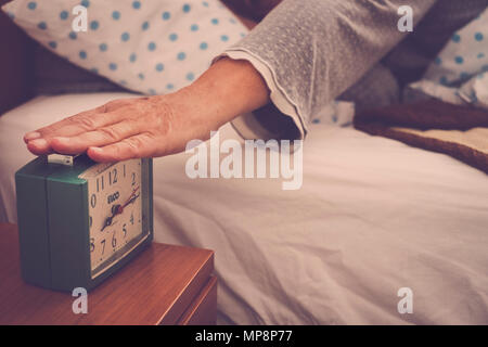 Caucasian people hand stop the alarm clock at the wake up in the morn ing. Senior woman - Stock Image
