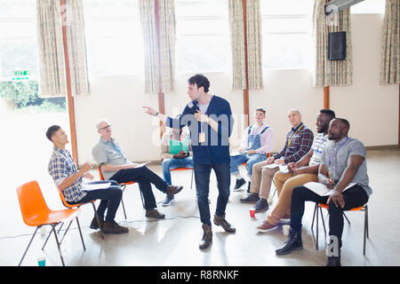 Man talking, leading group therapy - Stock Image