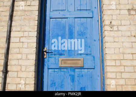 Brass door letterbox on a blue vintage front door on a  yellow brick wall - Stock Image