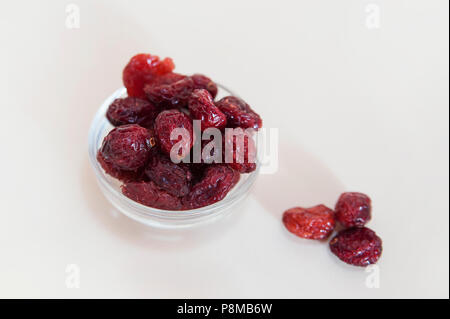 Dried sweetened cranberries in a glass bowl - Stock Image
