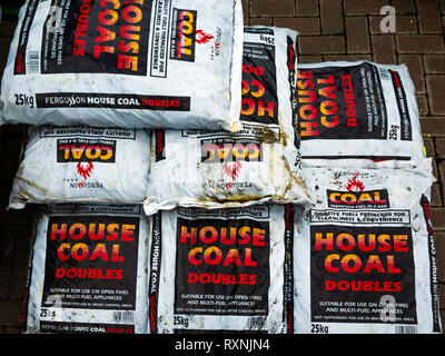 Stack of bags of Traditional House Coal for sale in a garden centre - Stock Image