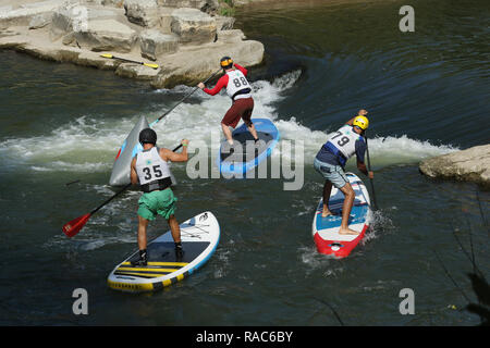 Standup Paddleboarders race around a buoy. At the Whitewater feature in the Mad River. Wagner Subaru Outdoor Experience at Eastwood Metro Park, Five R - Stock Image