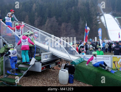 Young kids play on the 'baby ski jumping hill' for children. Ljubno ob Savinji, Slovenia. - Stock Image