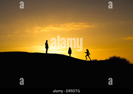 Silhouette of a father with his two children at sunset. UK. - Stock Image