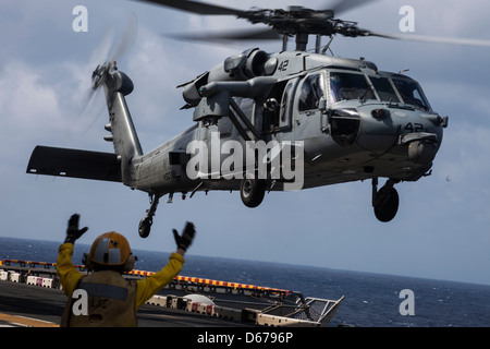 An MH-60S Seahawk takes off from the flight deck of the USS Kearsarge (LHD 3), at sea, March 18, 2013. The 26th - Stock Image