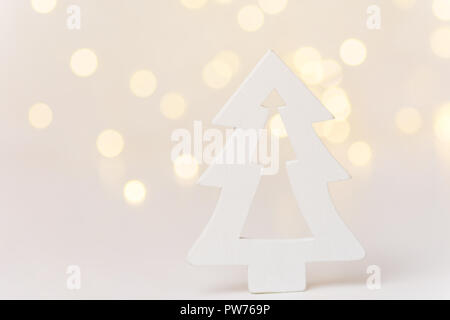 Wooden ornament Christmas tree in forest golden bokeh garland lights white background. New Years holiday magic atmosphere. Greeting card banner poster - Stock Image