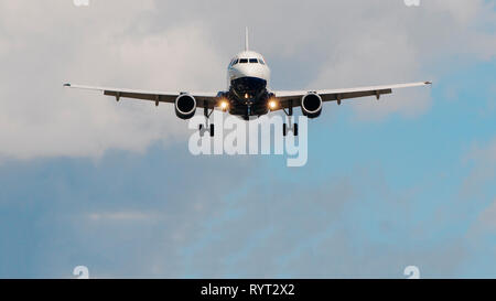 Airplane landing at the airport, front view with copy space - Stock Image
