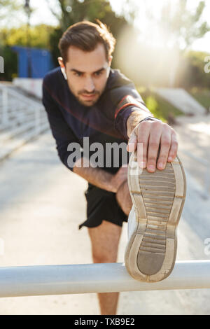 Image of a handsome young strong sports man posing outdoors at the nature park location make stretching exercises with mobile phone holder on hand lis - Stock Image