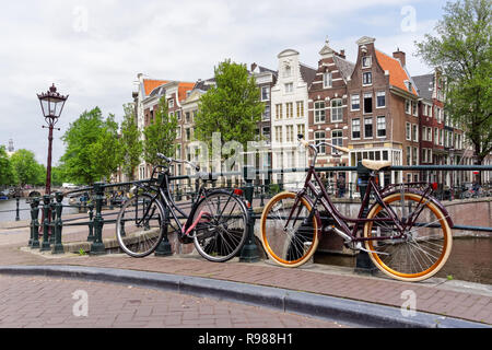 Dutch bicycles parked along the canal in Amsterdam, Netherlands - Stock Image