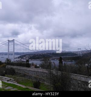 Suspension Bridge In City Against Cloudy Sky - Stock Image