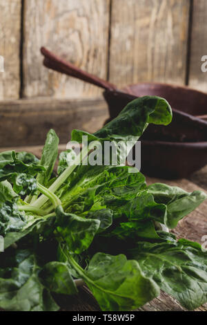 Fresh raw organic spinach on wooden table, plant based food, close up, selective focus, food ingredients - Stock Image