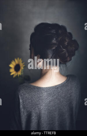 Rear view of woman with sunflower at home - Stock Image