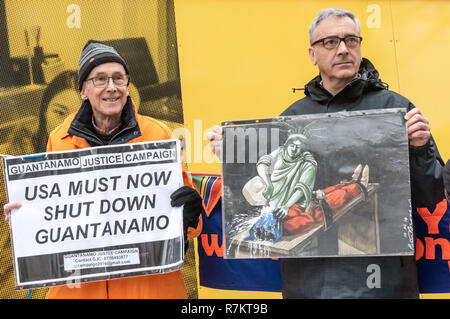London, UK. 10th December 2018. Protesters with posters, one showing the statue of Liberty waterboarding a prisoner opposite the US Embassy at the final 'Shut Guantanamo!' monthly protest of 2018 at the US Embassy on the 70th anniversary of the Universal Declaration of Human Rights (UDHR). This declared 'No one shall be subjected to torture or to cruel, inhuman or degrading treatment or punishment' and 'No one shall be subjected to arbitrary arrest, detention or exile.' Guantanamo still has 40 detainees. Credit: Peter Marshall/Alamy Live News - Stock Image