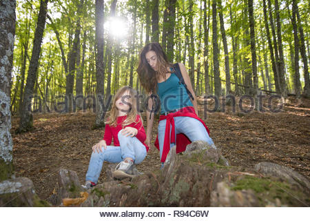 four years age blonde child sitting on trunk near mother woman in forest of chestnut trees in autumn in backlight - Stock Image