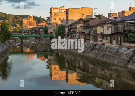 Reflections of the buildings on the banks of the Miyagawa River in Takayama at sunset - Stock Image