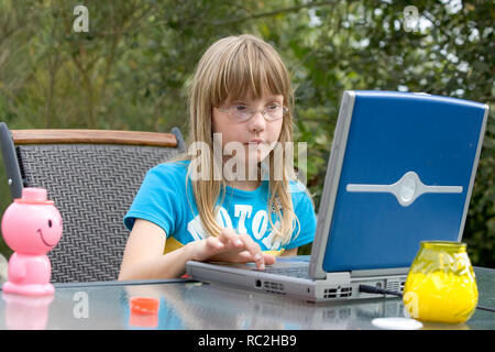 Young caucasian female child in the 2000s playing with a laptop computer in the back garden in summer. - Stock Image