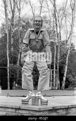 Elton John, singer, pictured at home in Virginia Water, in 1973.  He is playing for the camera, over 3 pictures, pulling faces and showing off his hairy legs and latest platform boots, which are a 5 platform size, and 8 inches high. They are silver and red, with his initials on, and were made to measure in about three days by Ken Todd of Kensington Market.  Picture taken 20th March 1973 - Stock Image