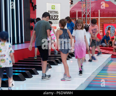 Montreal, Canada. 6/29/2018. Children play on the musical piano keys  at the Montreal International Jazz Festival. Credit: richard prudhomme/Alamy Live News - Stock Image