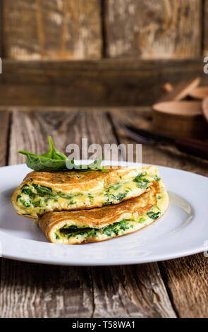 Baby spinach and parmesan cheese omelette, healthy vegetarian breakfast or brunch on wooden rustic table, close up, selective focus - Stock Image
