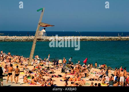 Spain Barcelona beach Platja de la Barceloneta baywatch tower people crowded beach - Stock Image