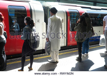 A smart dressed Indian man wearing a white suit and shoes awaits his train. London Underground, UK. - Stock Image