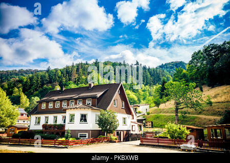 Idyllic house in the German alps with green forest in the background under a blue sky in the summer - Stock Image