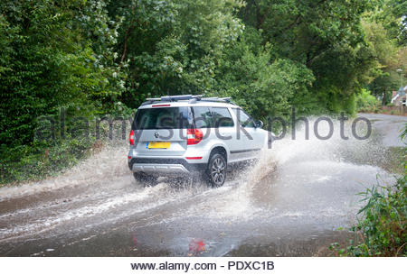 Southampton UK 10th August 2018  It never rains but it pours. After weeks of drought thunder storms with strong winds whip along the South Coast. Along Weston Shore in Southampton cars pass through a flooded road. Credit: Richard Wareham Fotografie/Alamy Live News - Stock Image