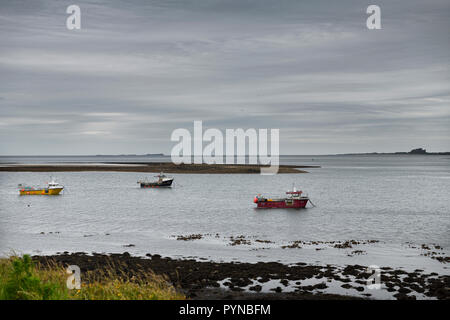 Three boats at low tide on Holy Island of Lindisfarne with Bamburgh Castle and Farne Islands on the North Sea England UK - Stock Image