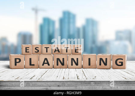 Estate planning sign on a wooden pier with tall buildings in the background - Stock Image