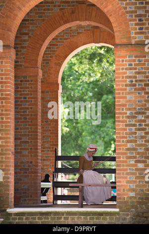 Woman in traditional dress sitting at Williamsburg, Virginia, USA - Stock Image