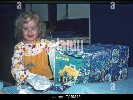 Archival 1970s young toddler girl removes wrapping paper from a Fisher Price play family house toy Christmas day present in box bedroom England UK - Stock Image