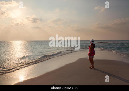 Maldives holiday - a woman tourist watching the sunset over the Indian Ocean from the beach, Concept - travel; Rasdhoo atoll, the Maldives Asia - Stock Image