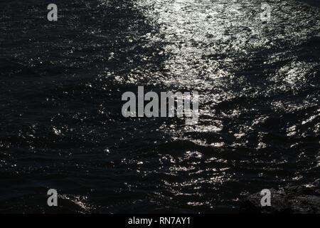 Sea water slowly waves under the last sun light producing beautiful patterns. - Stock Image