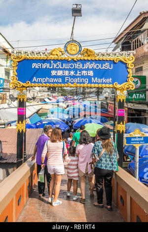 Amphawa, Thailand - 7th October 2018: Tourists crossing bridge under sign in English, Thai and Chinese, A floating market is held every weekend. - Stock Image