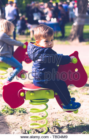 Small boy sitting on a red wooden horse swing in a - Stock Image