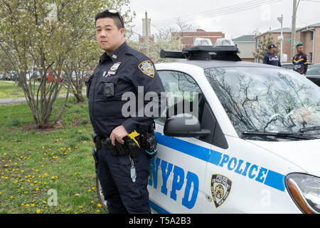 Portrait of a Chinese American police office on duty at a cricket tournament in Baisley Pond Park in Jamaica, Queens, New York City. - Stock Image